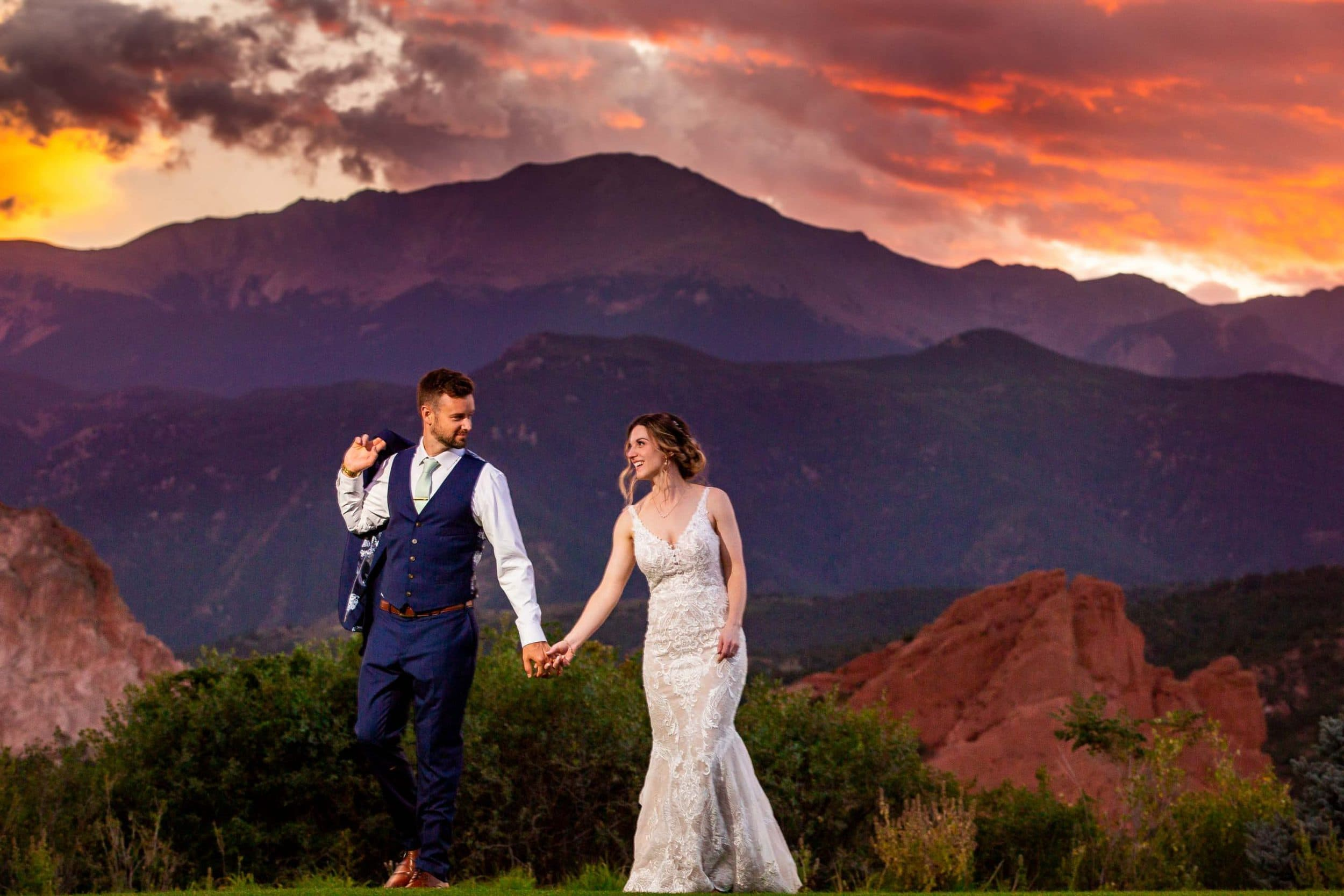 A bride and groom walk hand in hand at sunset with Garden of the Gods in the background.