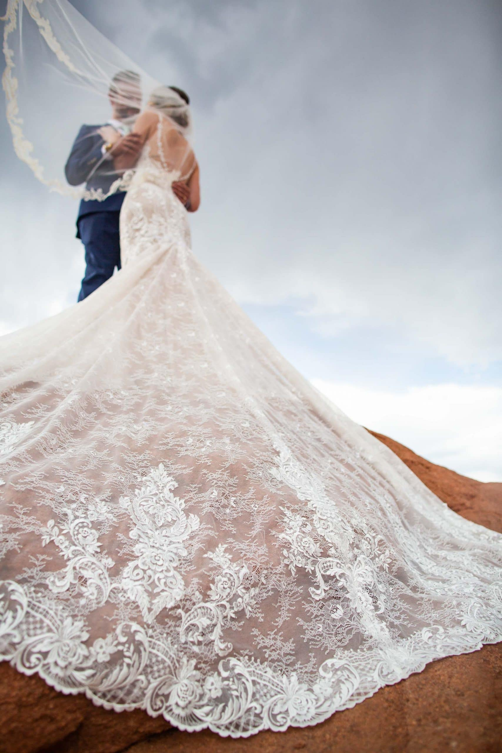 A close up of a lace wedding dress on a red rock at Garden of the Gods