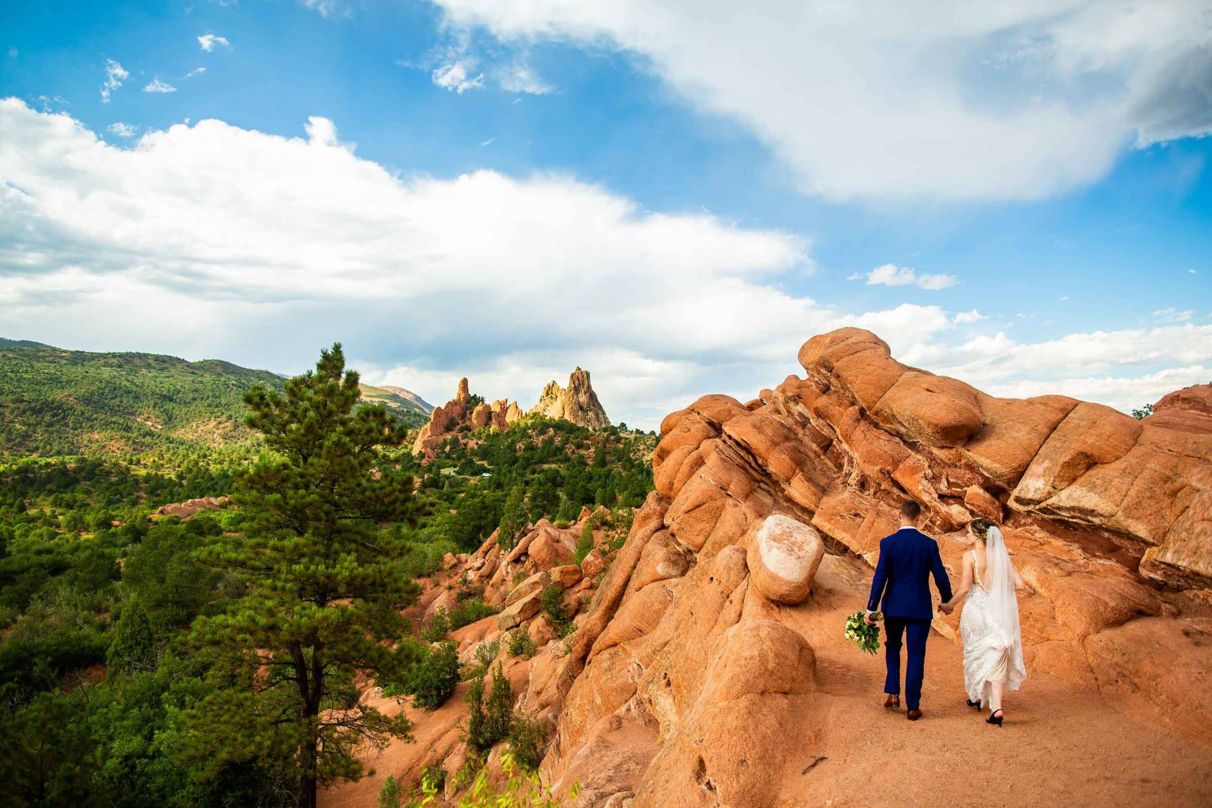A wedding couple walks towards the rocks at Garden of the Gods