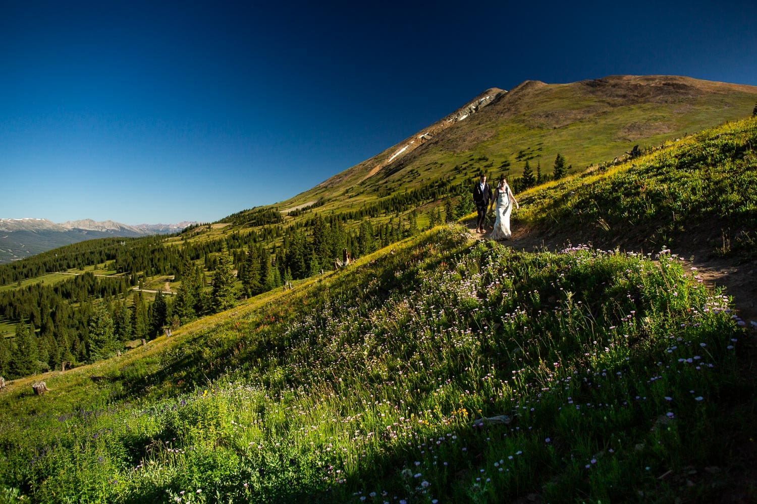 A hiking elopement couple with backpacks takes a trail near Breckenridge, Colorado.