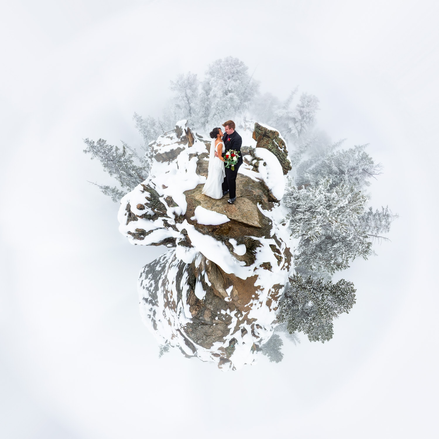 A tiny planet of a winter wedding couple in the mountains.