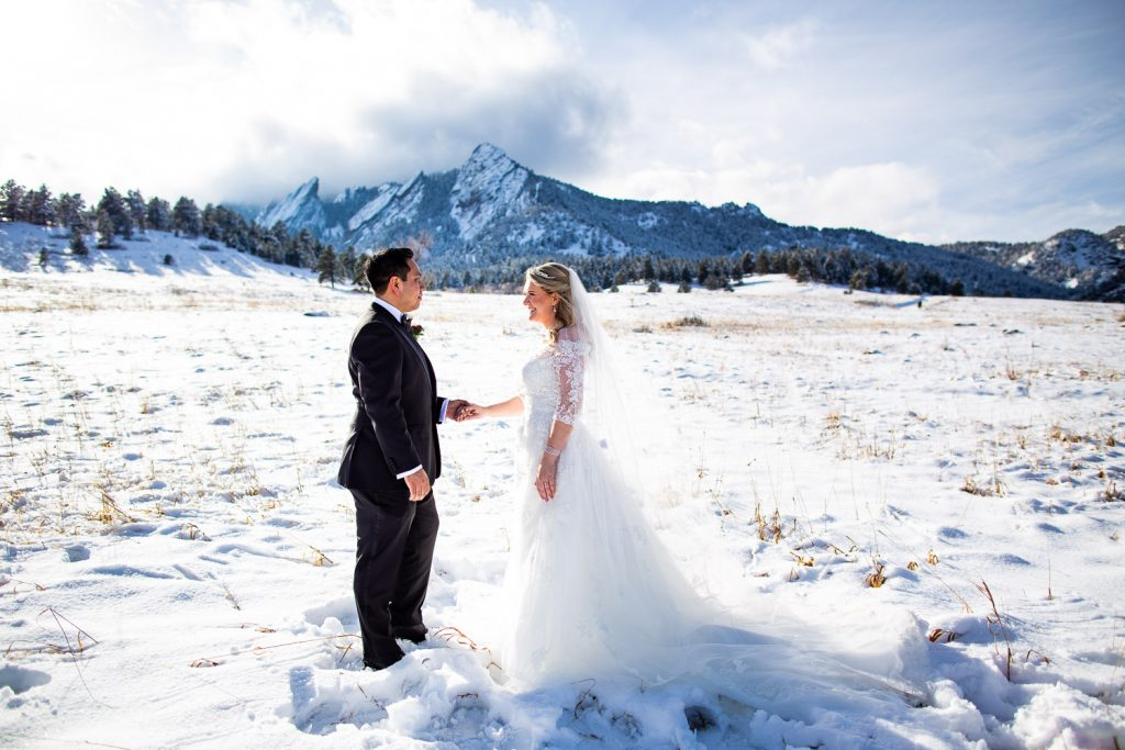 A wedding couple stands in front of the flatirons in boulder with a fresh coat of snow.