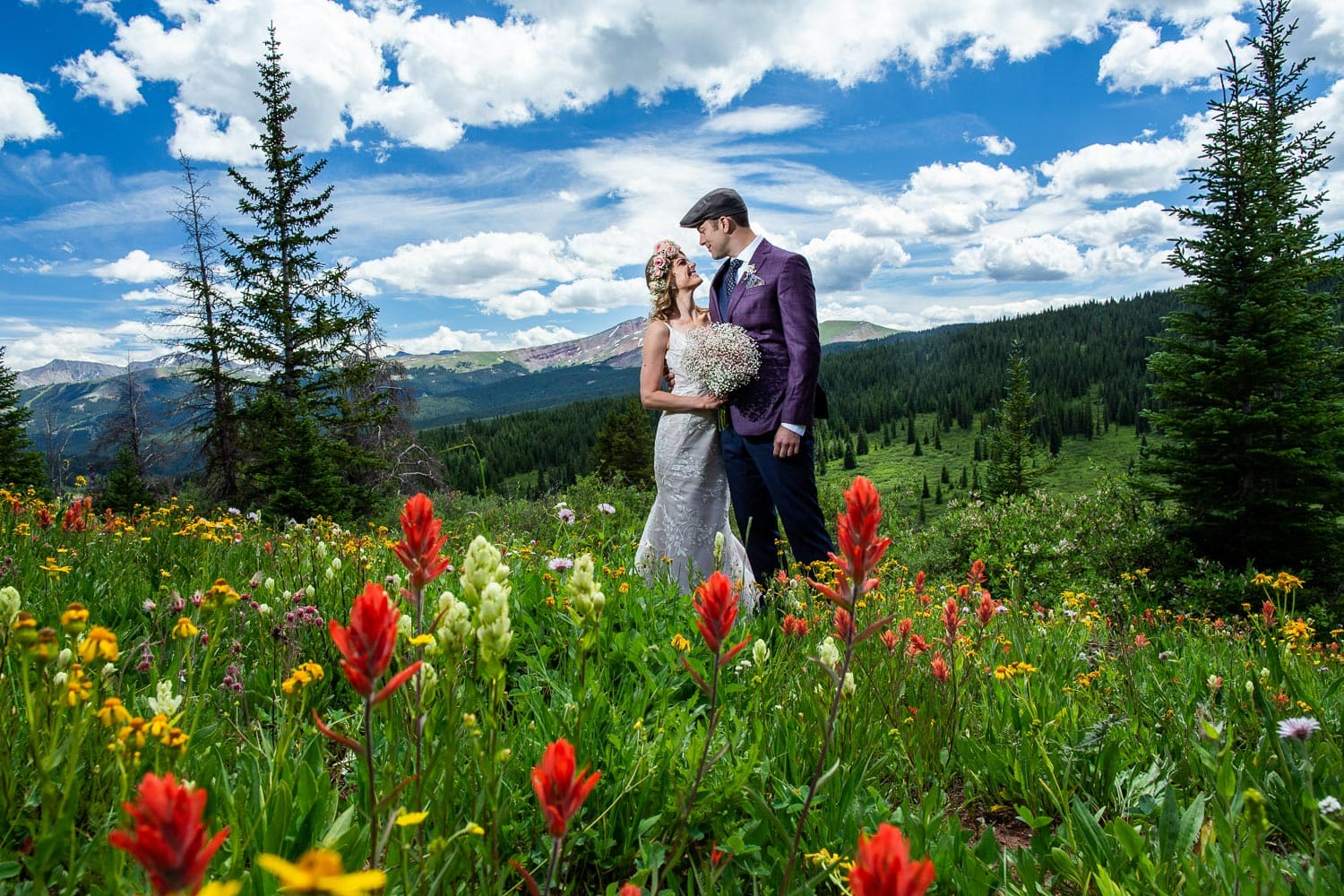 A boho bride and a groom in a purple jacket on the side of a mountain covered in wildflowers.