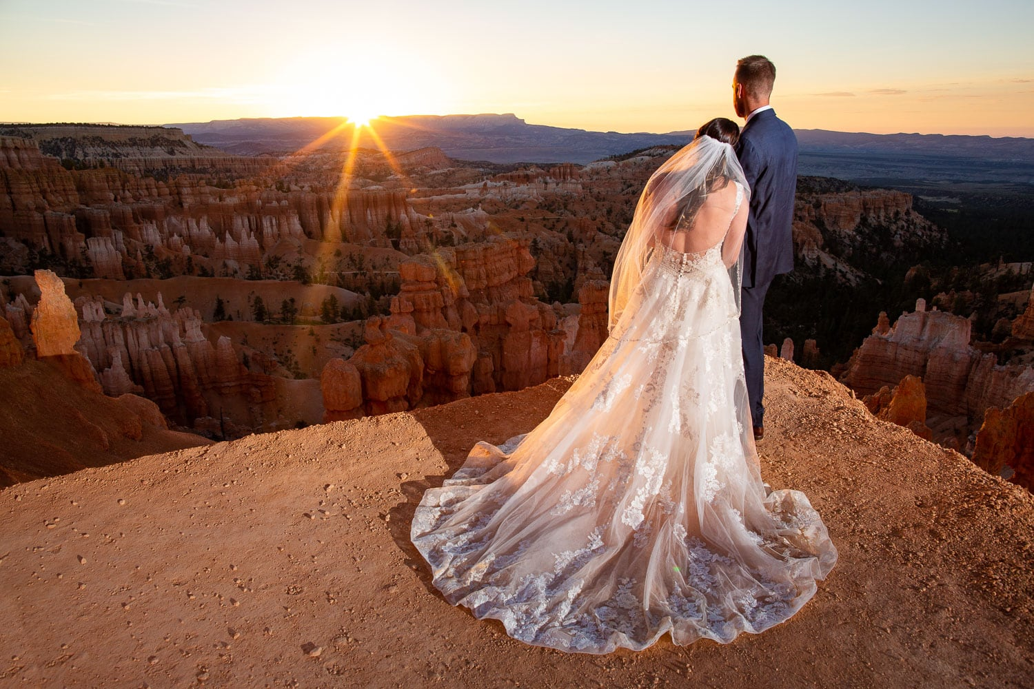 A bride and groom watch the sun rise over bryce canyon.