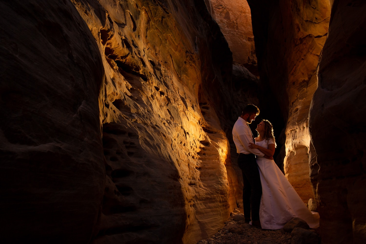An adventurous wedding couple is photographed in a slot canyon.