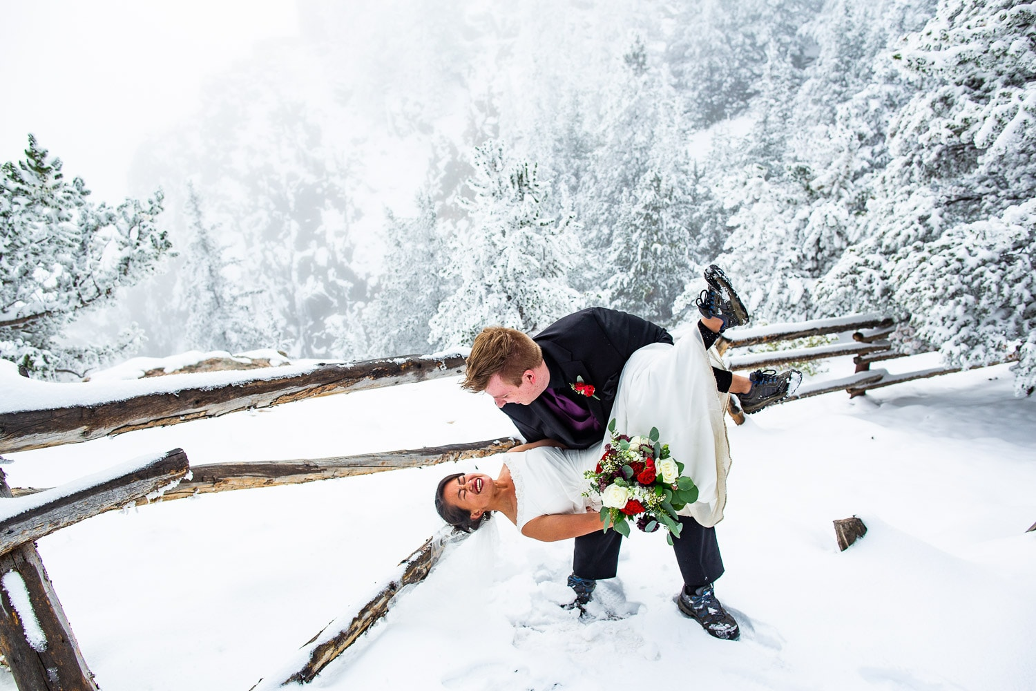 A groom dips his bride wearing hiking boots in the mountains, surrounded by snow.