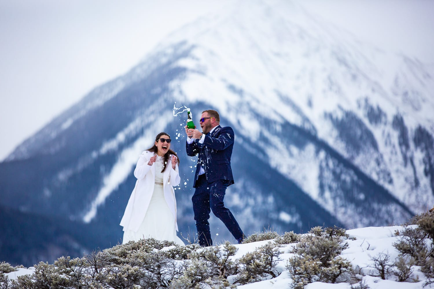 An elopement couple spray champagne in front of a large mountain.