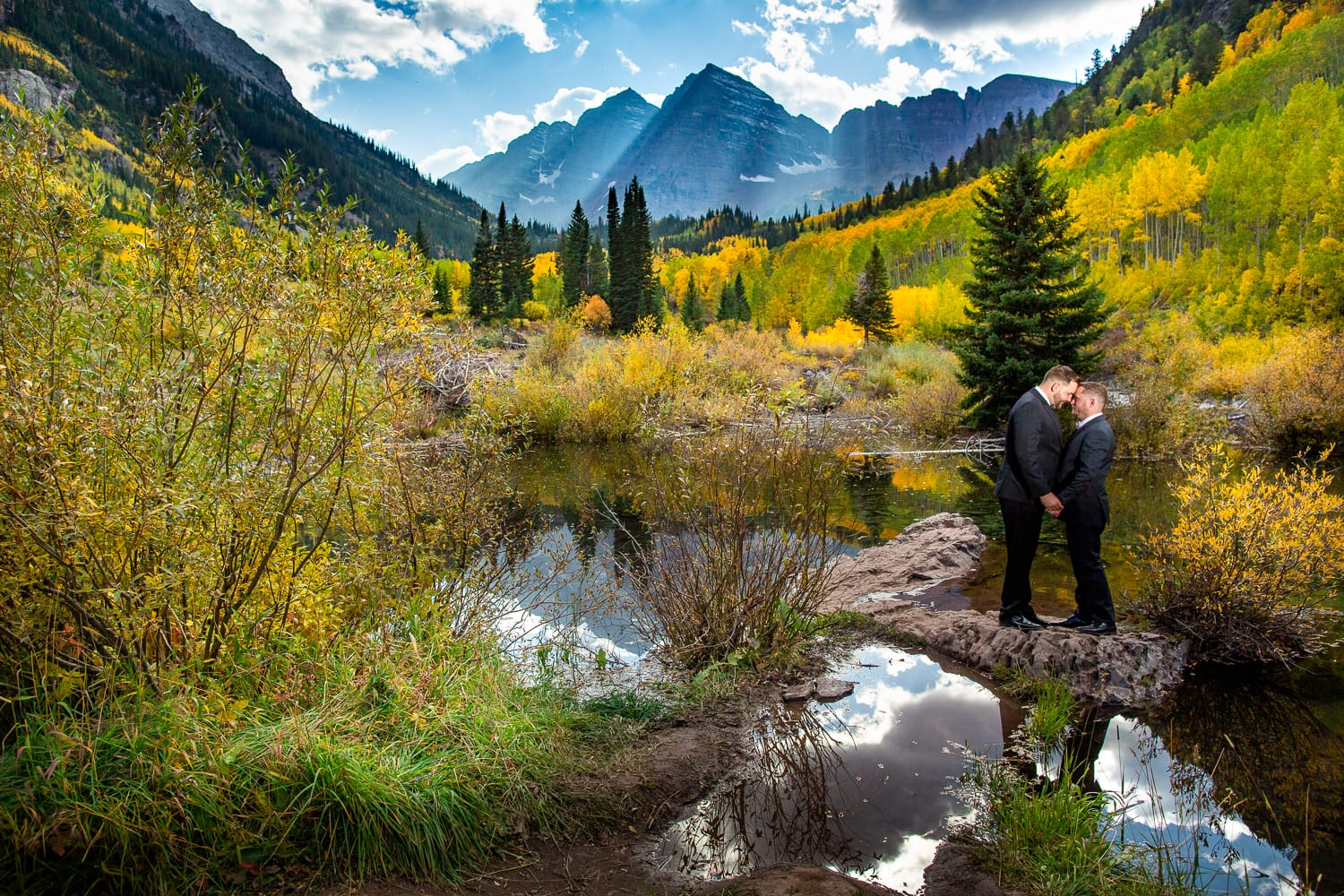 Two grooms share a romantic moment at the Maroon Bells in the fall.