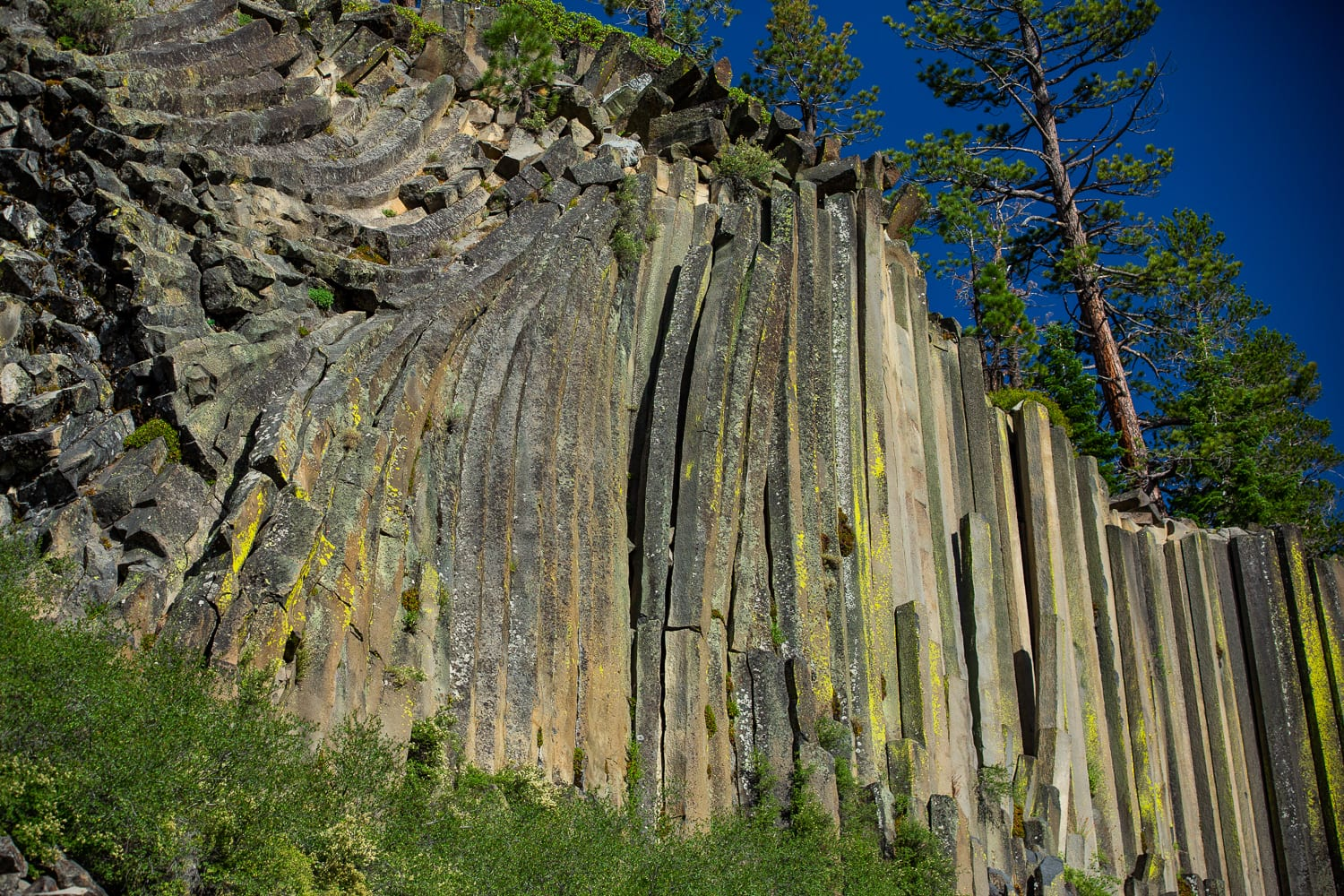 Hexagonal rock pillars tilt at Devil's postpile national monument.