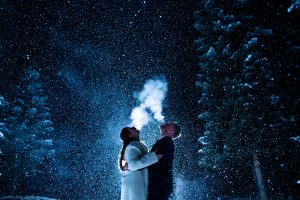 A bride and groom see their breath as snow falls around them after dark.