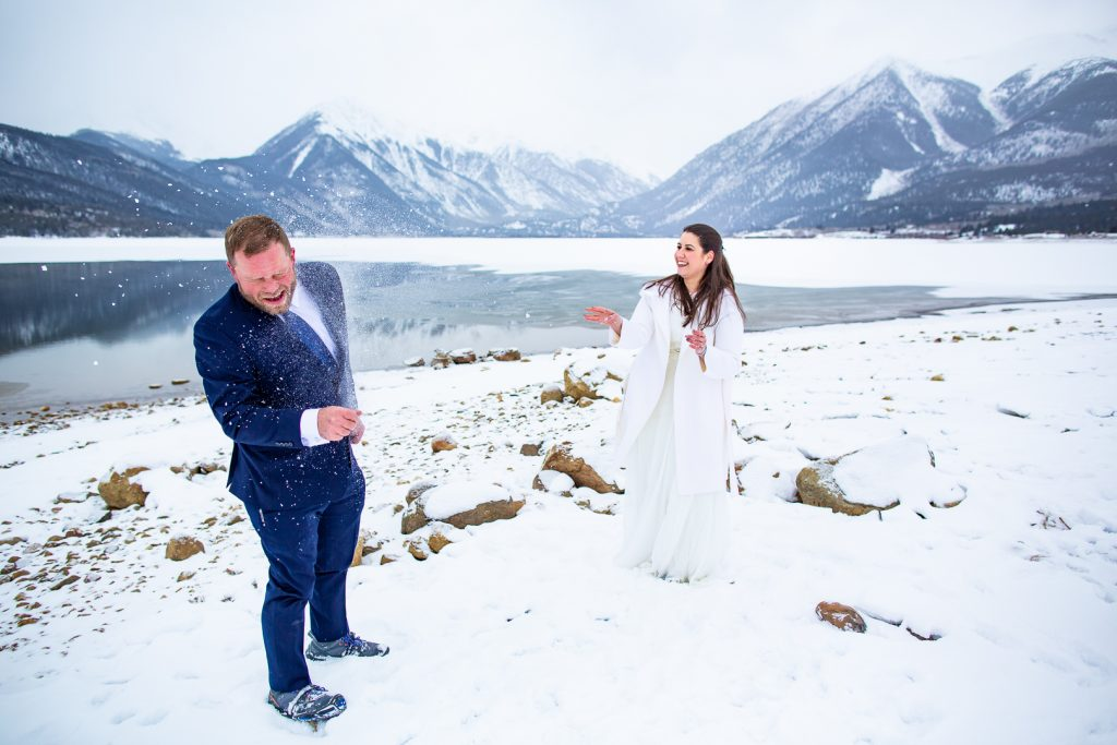 A couple on their elopement day throwing snowballs in the mountains.