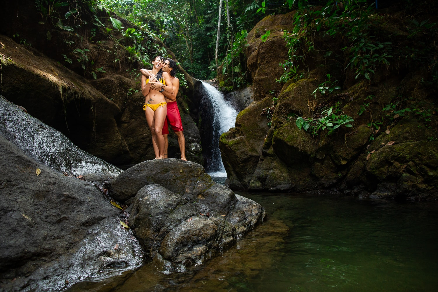 A couple kiss in front of a Costa Rica waterfall.