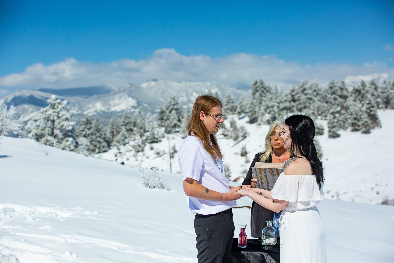 A bride and groom have an elopement ceremony in the winter on a mountainside.