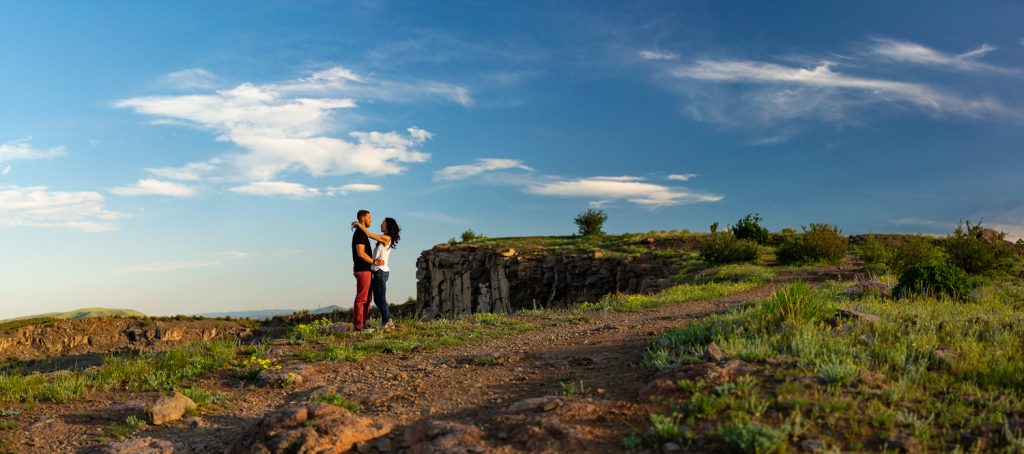 An engaged couple look at each other on top of North Table Mountain in Golden, Colorado.
