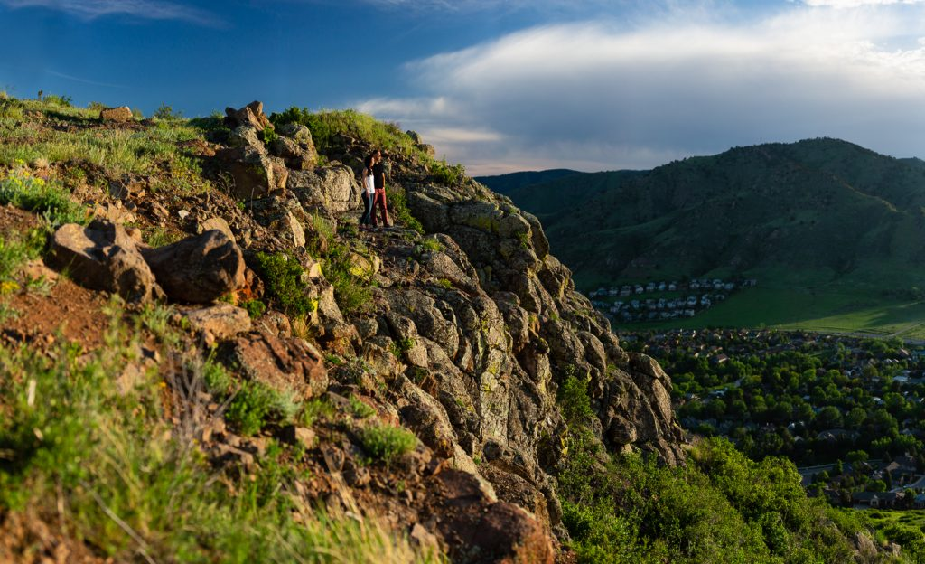 An engaged couple look out over Golden, Colorado from North Table Mountain.