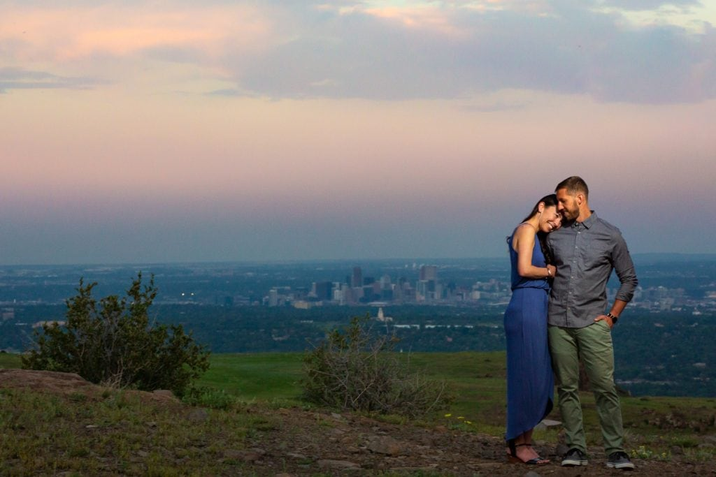 A couple cuddles up at sunset with the Denver city skyline in the background of their engagement photo.