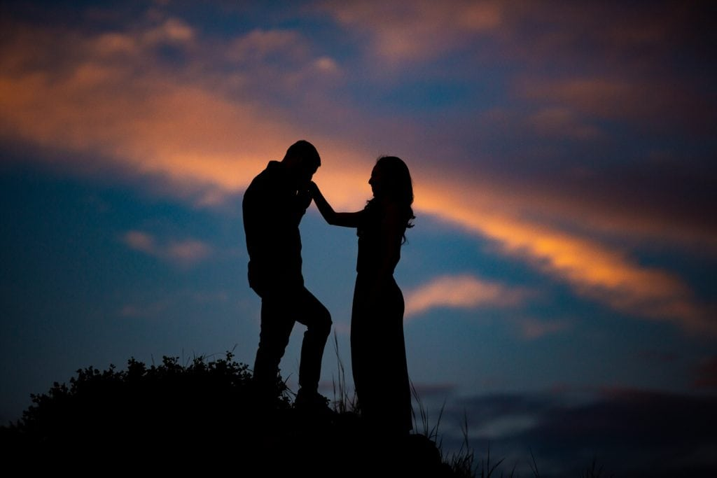 A silhouette of a man kissing his fiancee at sunset.