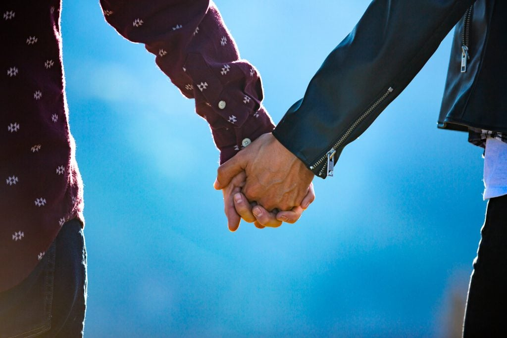 Two men hold hands at their engagement photo session in telluride.
