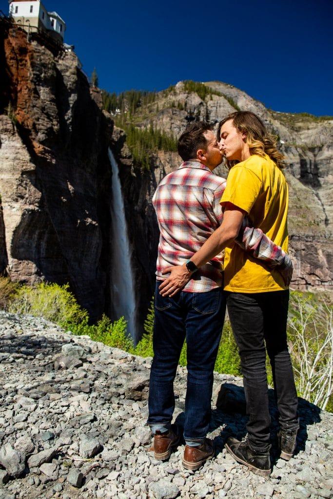 Two men kiss in front of Bridal Veil falls in telluride, Colorado.
