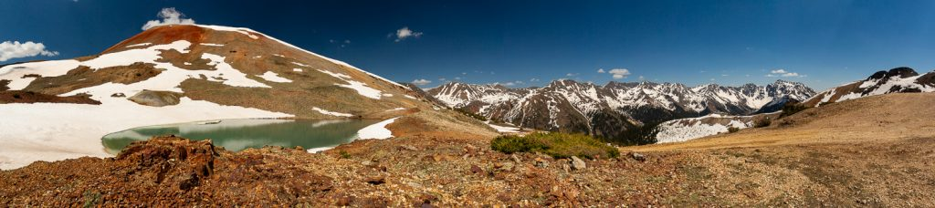 An alpine lake and snowy mountain peaks are visible from an off road trail in Ouray.