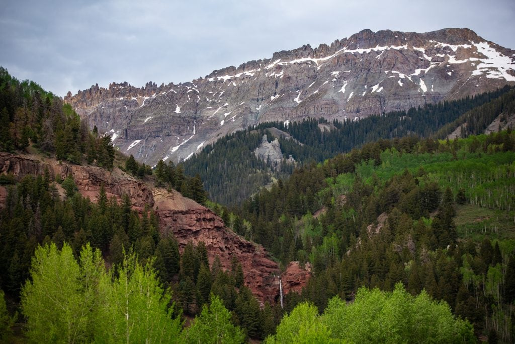 A waterfall, aspen trees, and exposed red rock form layers in front of Mt Sneffels near Telluride.