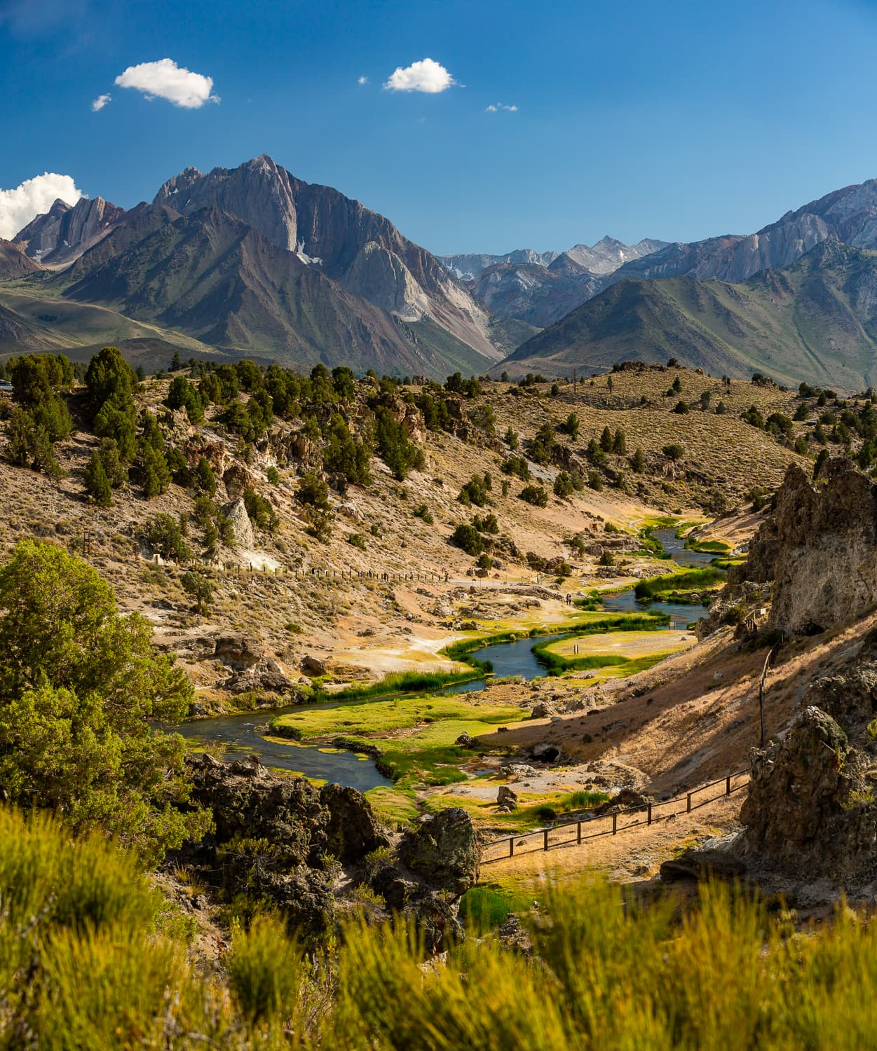 A colorful landscape photo looking west over the winding hot creek with mammoth mountain in the background.