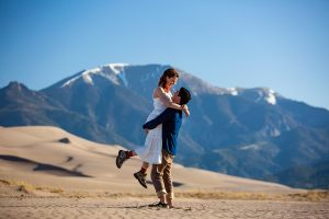 A groom lifts his bride wearing hiking boots at the Great Sand Dunes in Colorado.