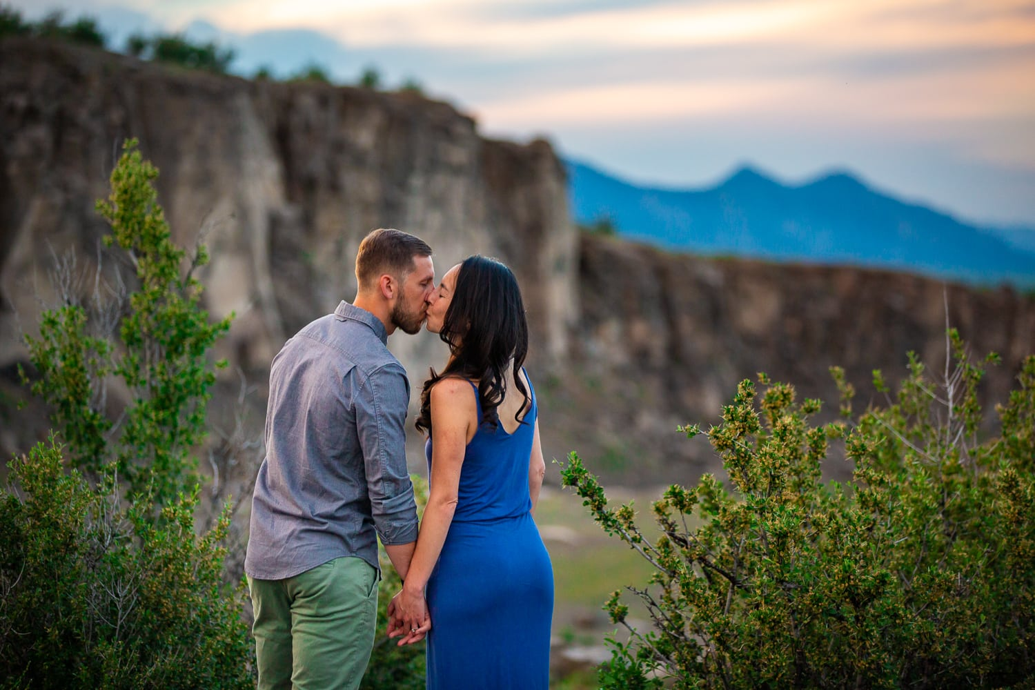 An engagement photographer in Golden Colorado takes a photo of a couple kissing with mountains in the background.
